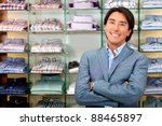 Smiling shop manager in front of tshirts - stock photo