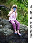 Little girl sitting on the rocks with mobile phone taking snapshots - stock photo