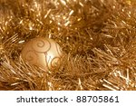 Golden Christmas decorations: bauble and tinsel. - stock photo
