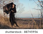 Beautiful young girl with a black umbrella stands against the background of autumn trees and the beach. - stock photo