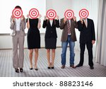 Group of business people holding a target against their faces - stock photo