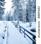 Winter path - bridge to the wilderness in Rovaniemi, Lapland, Finland - stock photo