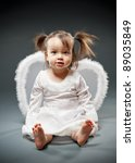Baby girl sitting and dressed as an angel - stock photo
