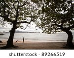 Small fishing boat resting at quiet beach - stock photo