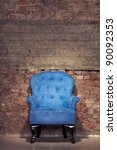 An antique blue velvet chair near the grungy brick wall - stock photo