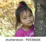 Sad lonely Asian girl by tree - stock photo