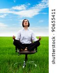 businesswoman sitting in lotus position on armchair in green field - stock photo
