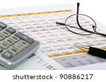 Financial charts with pen, calculator and glass. - stock photo