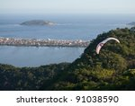 Hang glider flying over  coastal area - stock photo