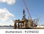 Closeup of ocean oil rig docked in Halifax Harbor, Nova Scotia, Canada. The city Halifax can be seen in the background. - stock photo