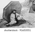 Woman with umbrella at beach - stock photo