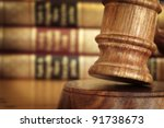 Gavel, with defocussed law books behind. - stock photo