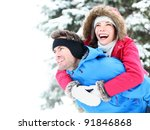 Winter couple piggyback in snow smiling happy and excited. Beautiful young multiracial couple, Asian woman, Caucasian man piggybacking - stock photo