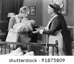 Mother giving her sleeping baby to a nanny - stock photo
