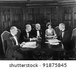 Group of men sitting with a young woman in a boardroom - stock photo