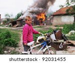 VUCITRN, KOSOVO - JUNE 26: A young ethnic Serb boy watches his house burn to the ground in Vucitrn, Kosovo, on Saturday, June 26, 1999. Ethnic Albanians burned ethnic Serb houses after NATO peacekeepers entered the province. - stock photo