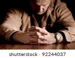 Dark, emotional image of clasped hands on troubled man - stock photo