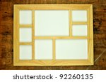 Empty wooden picture frame, on rustic wooden background - stock photo