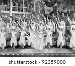 Group of dancers standing on a stage with their arms in the air and a drink in their hands - stock photo