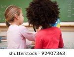 schoolgirls looking at a globe... | Shutterstock . vector #92407363