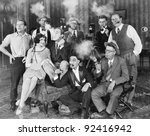 Group of people sitting in a living room smoking - stock photo