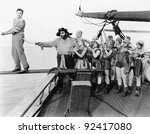 Group of pirates trying to push a young man over a plank - stock photo
