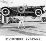 Strong man lifting a car over his head - stock photo
