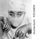 Surgeon in a surgical mask operating - stock photo