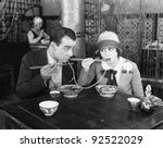 Couple sharing a noodle in a restaurant - stock photo