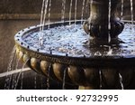 Detail of an old classic style stone fountain with flowing water - stock photo