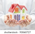 Colorful house in hands - stock photo