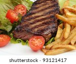 Closeup of a grilled steak with french fries, lettuce and cherry tomatoes - stock photo