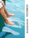 boy hanging feet over water - stock photo