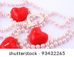 Heart shape red candles and necklace isolated on grey background. - stock photo