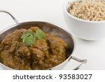 Small photo of Goan Chicken Xacuti served with pilau rice on a white background.