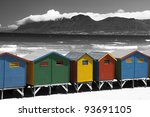 Beach huts with Black and White  mountain backdrop and ocean with strong contrast - stock photo