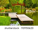 Japanese garden scene - jetty and bridge in the background - stock photo