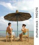 couple on beach under umbrella | Shutterstock . vector #940196