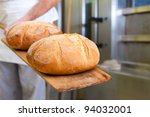 Male baker baking fresh bread in the bakehouse - stock photo