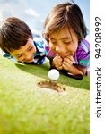 Young golf players staring at the ball to see if it goes in the hole - stock photo