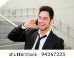 Portrait of a handsome young business man smiling and talking on mobile phone - stock photo