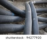 Heap of black plastic pipes at construction site - stock photo