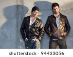 Young and handsome men, casually leaning against the wall. - stock photo