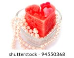 Heart shape red candle and necklace isolated on grey background. - stock photo