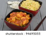 Chinese sweet and sour chicken served egg fried rice and prawn crackers. - stock photo