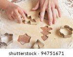little girls and mother cutting cookies, hands only - stock photo