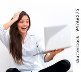 Young attractive woman  with surprised face expression  sitting on floor with laptop. - stock photo
