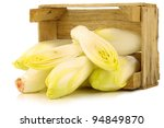 fresh chicory and two cut halves in a wooden crate on a white background - stock photo