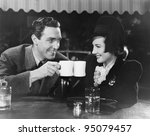 Couple toasting with mugs - stock photo