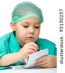 Cute little girl is playing doctor prescribing treatment in her notepad, isolated over white - stock photo